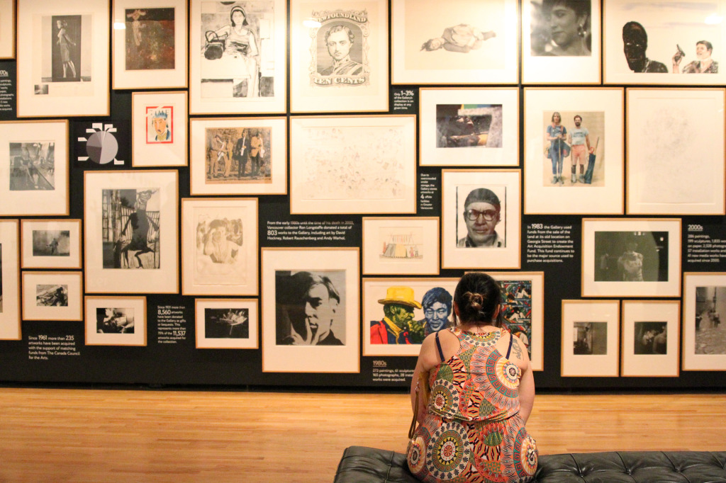Woman views the wall of art at FUSE: The Noise of Silence at the Vancouver Art Gallery